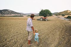 Father shows his toddler son an old tractor on a plowed field among hills. Countryside in Cyprus royalty free stock photo