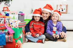 Father And Siblings Sitting By Stacked Christmas Stock Photos