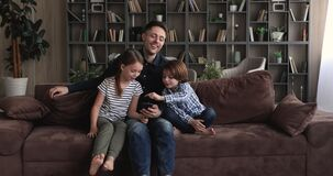 Father sit on sofa with children having fun use smartphone