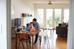 Father Sits At Table And Plays With Baby Son At Home Royalty Free Stock Photo