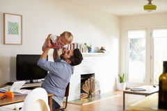 Father Sits At Table And Plays With Baby Son At Home Royalty Free Stock Photography
