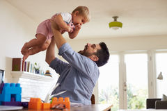 Father Sits At Table And Plays With Baby Son At Home Stock Photography