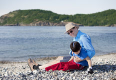 Father sitting on beach playing with disabled son Royalty Free Stock Photo