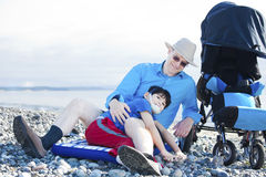 Father sitting on beach playing with disabled son Royalty Free Stock Images