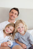 Father sitting on the bed with his children Stock Images