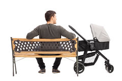 Father sitting on bench with a baby stroller Royalty Free Stock Photo