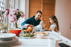 Father sitting on a chair and and his little daughter standing next to his look at the tiny baby lying on the table in stock photo