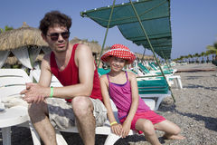 Father sitting on chaise longue on beach. Stock Photo