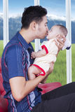 Father sitting on couch while kissing his son. Young father with casual clothes sitting on sofa while kissing his son and enjoy togetherness at home Stock Image