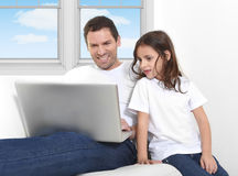 Father sitting on couch with 7 years old sweet little girl daughter using computer laptop Stock Image