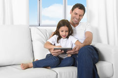 Father sitting on couch with 7 years old sweet little girl daughter using digital tablet pad Stock Photos