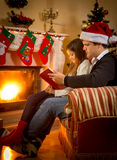 Father sitting with daughter at fireplace and telling story Royalty Free Stock Image