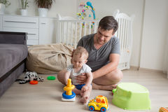 Father sitting on floor with his baby boy and playing with toys Royalty Free Stock Images