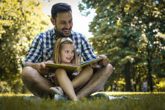 father sitting on grass with little daughter and reading Stock Image