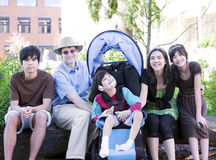 Father sitting with his biracial children and disabled son Stock Photography