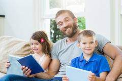 Father sitting with his kids on sofa Stock Photo