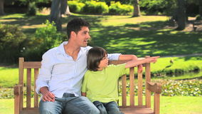 Father sitting with his son on a park bench stock footage