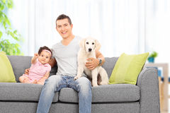Father sitting at home with his daughter and puppy Stock Photo