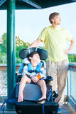 Father sitting by lake with disabled son in wheelchair Stock Photos