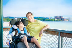 Father sitting by lake with disabled son in wheelchair Stock Photography