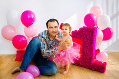 Father sitting next to her daughter. Little girl in a pink skirt. Father holding a baby in her arms. Little girl in a pink skirt. On a light background. First Royalty Free Stock Photography