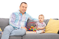 Father sitting on a sofa with his baby daughter Royalty Free Stock Photography