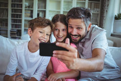 Father sitting on sofa with his children and clicking a selfie in living room Royalty Free Stock Images