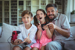 Father sitting on sofa with his children and playing video games Stock Images