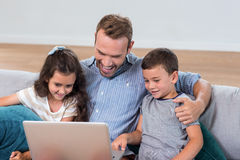 Father sitting with son and daughter and using laptop. Father sitting on sofa with son and daughter and using laptop royalty free stock photo