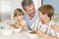 Father Sitting With Children As They Eat Breakfast Stock Photos