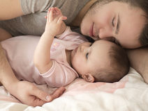 Father sleeping with baby daughter Stock Photo