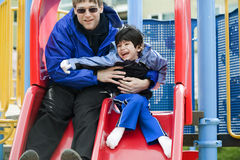 Father  sliding with disabled son Stock Images