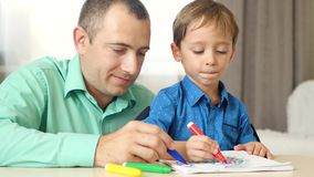 Father and a small boy draw, sitting at the table with coloured markers. A loving father spends time with his child. The