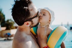 Father with small child with armbands standing by swimming pool on summer holiday. A father with small child with armbands standing by swimming pool on summer stock images