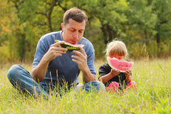 Father with a small daughter eat watermelon on the grass Stock Images