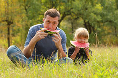 Father with a small daughter eat watermelon on the grass Stock Image