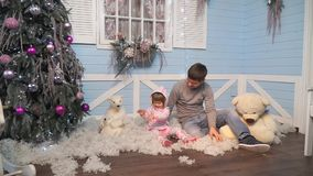 Father with a small daughter sitting under the tree and throwing snow stock footage