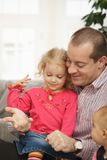 Father with small daughters. Smiling father sitting with small daughters talking playing at home Stock Photos