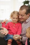 Father with small daughters. Smiling father sitting with small daughters talking playing at home Stock Photography