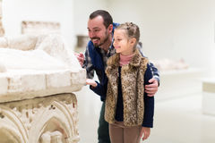 Father and small girl exploring old bas-reliefs Stock Photography