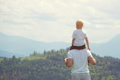 Father with a small son on his shoulders. Mountains on the backg. Round. Summer sunny day. Back view Royalty Free Stock Photo