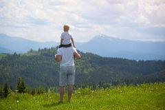 Father with a small son on his shoulders. Mountains on the backg. Round. Summer sunny day. Back view Royalty Free Stock Photos
