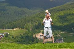 Father with a small son on his shoulders. Mountains on the backg. Round. Summer sunny day Royalty Free Stock Photography