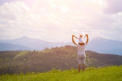 Father with a small son on his shoulders. Mountains on the backg. Round. Summer sunny day. Back view Stock Photos