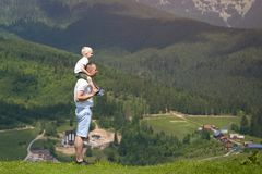 Father with a small son on his shoulders. Mountains on the backg. Round. Summer sunny day. Side view Royalty Free Stock Images