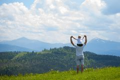 Father with a small son on his shoulders. Mountains on the backg. Round. Summer sunny day. Back view Stock Photo