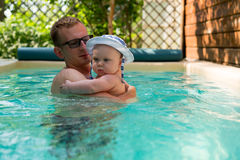 Father and small son in a panama hat swimming in the pool Royalty Free Stock Photo