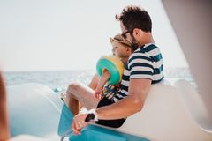 Father with small son sitting on boat on summer holiday. royalty free stock images