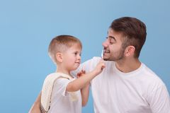 A father with a small son, a small boy will brush his daddy teeth with a toothbrush. On a blue background. A young father with a small son, dressed in white T stock photos
