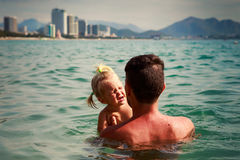Father and smiling little daughter in shallow sea water Royalty Free Stock Photography